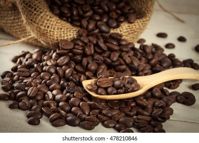 close up coffee bean on wooden spoon and pile of coffee bean out of sack with vintage color style.