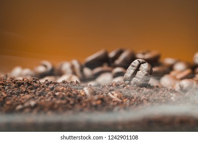 Close up Coffee beans over the cofee powder with smoke