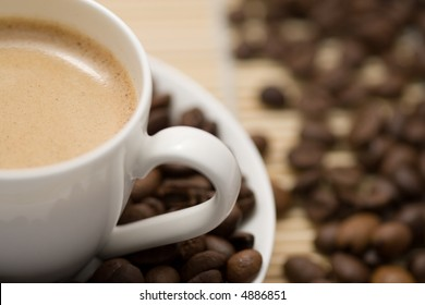 close up of coffee cup and saucer with coffee beans