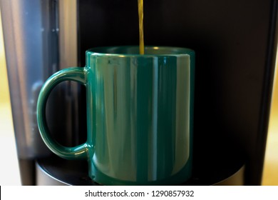 Close Up of Coffee Dripping from a Brewer into a Green Mug