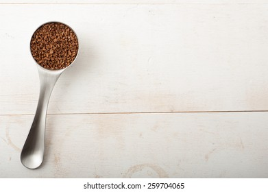 Close up of a coffee scoop filled with instant coffee