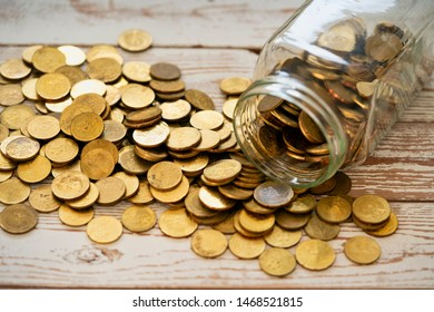 Close up coins in glass jar on wooden table. Coins scattered around.