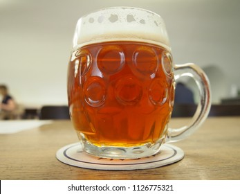 Close Up of a Cold 50cl Glass of Micro Brewed Fresh Czech Pilsner Style Lager Beer in a Dimpled Thick Glass Beer Mug with Handle on a Wooden Table in a Prague Microbrewery in Czechia