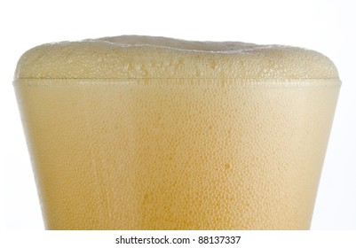 Close up of a cold frosted pilsner beer glass with all beer head over rim level