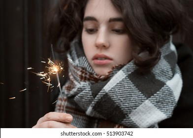 Close up cold portrait of young and beautiful brunette girl wearing warm scarf holding sparkler in her hand and looking on it.
