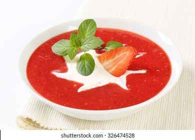 close up of cold strawberry puree with cream in white bowl