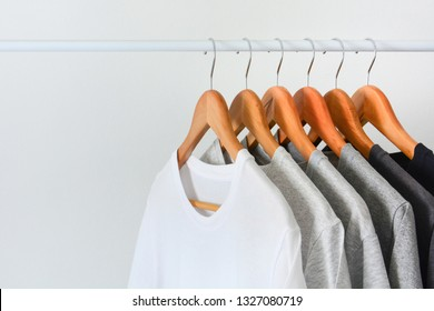 close up collection of black, gray and white color (monochrome) t-shirt hanging on wooden clothes hanger in closet or clothing rack over white background, copy space