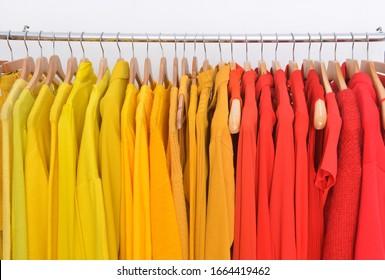 Nahaufnahme von  verschiedene gelbe und rote Kleidung, Mantel, Pullover, Hemd, Kleidung, Jacke auf einem Kleiderbügel