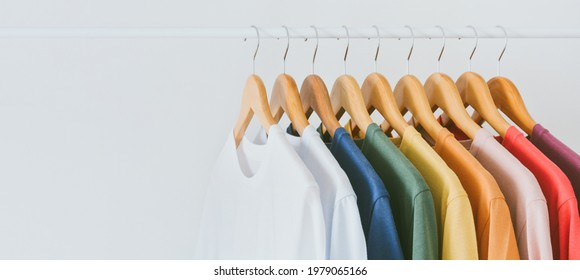 Close up a collection of pastel color t-shirts hanging on a wooden clothes hanger in closet or clothing rack over white background, copy space