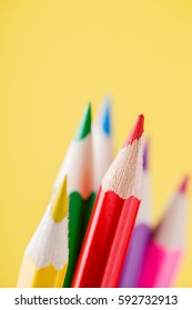 Close up of color pencils with different color over yellow background