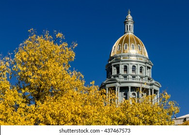Close up of Colorado USA State Capitol Building dome in Denver, CO on sunny autumn morning with changing tree around building