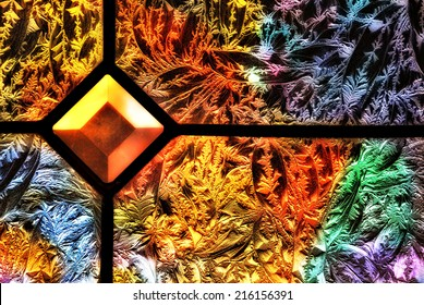 A close up of colored lights shining through a frosted glass window