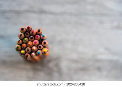 Close up colored pencils pile pencils nibs mixed color in cup on wooden table background.