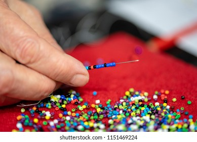 A close up of colorful beads on a red velvet surface and a hand with a needle beading the beads with a white and black blurred background.