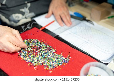 A close up of colorful beads on a red surface with a hand beading the beads on a needle and a white blurred surface in the background with pliers and a loom.