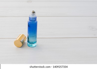 Close up of colorful blue ombre essential oil roller bottle with gold lid on white wooden background