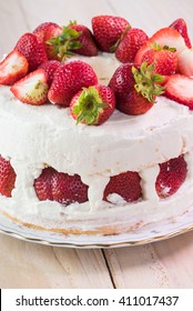 Close up of  colorful, creamy, delicious strawberry cake on wooden background.