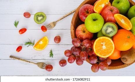 close up colorful fresh fruit orange apple grape kiwi fruit full of vitamin c on white wooden table