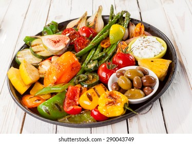 Close Up of Colorful Grilled Vegetable Bounty on Cast Iron Pan with Olives and Dip Resting on White Painted Wooden Picnic Table