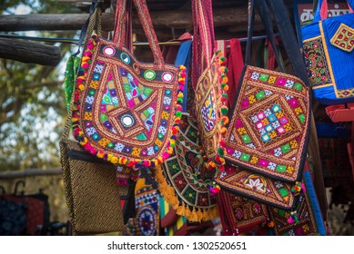 Close up of colorful handbags with Rajasthani embroidery work displayed outside street shop at tourist place.