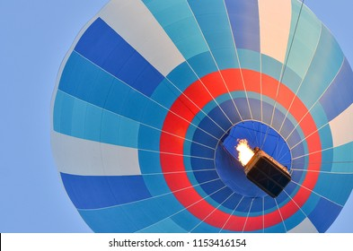 Close up of a colorful hot air balloon in blue sky. Bottom view.