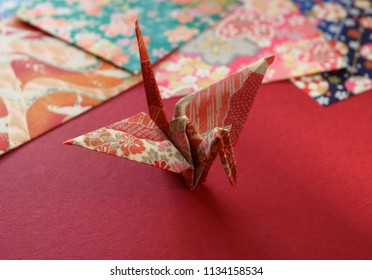 Close up of a colorful Japanese origami paper crane on a red texture with a stack of patterned origami papers in the background.