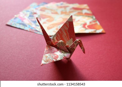 Close up of a colorful Japanese origami paper crane on a bright red texture with a stack of patterned origami papers in the background.