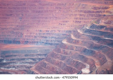 Close up colorful layers of industrial open cut layers at mining site, deep man made hole to excavate minerals and other resources.
