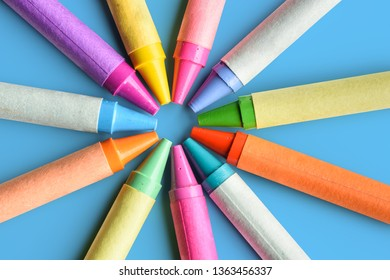 Close up of colorful pastel crayons on blue background