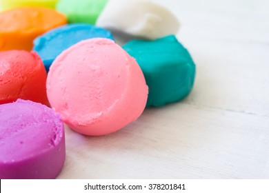 close up of colorful playdough on wooden table.