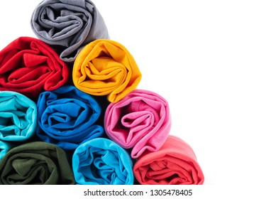 Close up Colorful of rolls cotton T-shirt made to Pyramid shape isolated on white background.