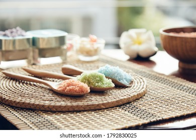 Close up of colorful salt spa in wooden spoon placing on reed mat