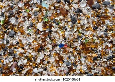 Close up of colorful smooth and rounded tiny pieces of sea glass making up the majority of the sand on the shore of  Glass Beach by Port Allen, on Kauai, Hawaii, a popular tourist attraction.