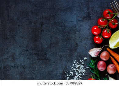 Close up of colorful spices and fresh vegetables for cooking on dark metal background with space for text. Top view. Bio Healthy food ingredients.