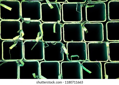 close up colorful steel profile pipe of square shape pattern texture on stack warehouse of steel products.