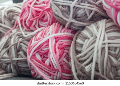 Close up colorful yarn texture background, dark brown cyclamen pink and pastel creamy beige strains, coiled in ball skein. Knitting and crochet, home craft work. Winter color combination for styling.