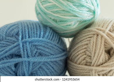 Close up colorful yarn texture background, pastel brown blue green and creamy beige strains, coiled in ball skein. Knitting and crochet, home craft work. Winter color combination for styling.