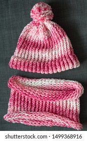 Close up colorful yarn texture of pink white hat and scarf. Shallow depth of focus. Knitting and crochet, craft work concept. Winter clothes, kids fashion. Color combination for styling and dressing.
