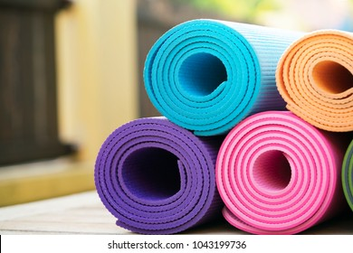 close up of colorful yoga mat on the table, sport and healthy concept