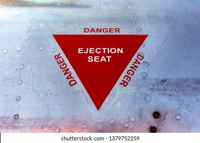 Close up colour photograph of military aviation warning of ejection seat printed on worn shiny aluminium shell.