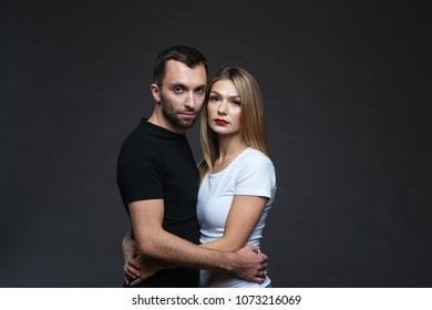 Close up colour portrait of stylish young couple, pretty woman and handsome man embracing against plain studio background