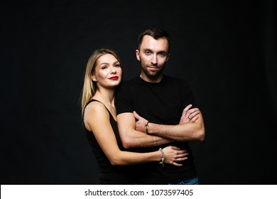 Close up colour studio portrait of stylish young couple, pretty woman and handsome man smiling and looking to the camera, against plain studio background.