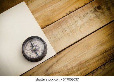 close up compass and old boo on wooden background