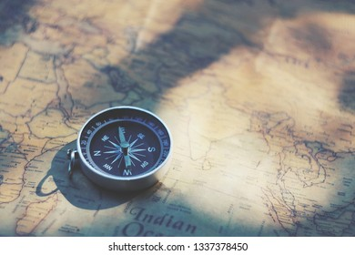 close up compass on map paper, travel and lifestyle concept, vintage tone
