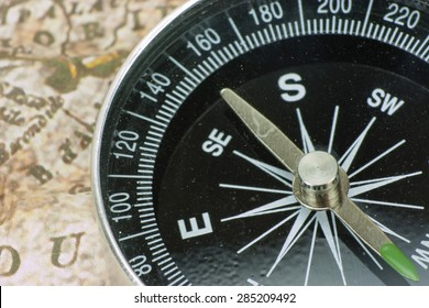 Close up of a compass on an old map