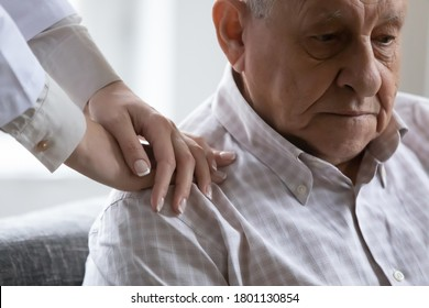 Close up compassionate young female doctor holding hands on shoulders of depressed old retired patient. Head shot stressed unhappy unhealthy elderly man needs psychological help support at checkup.