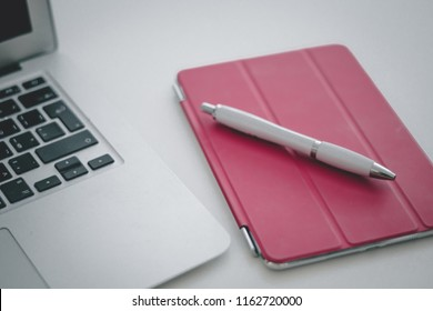 Close up composition: blank screen laptop computer, empty page notebook planner, pen on wooden table with visible wood texture pattern. Background, copy space, top view, flat lay.