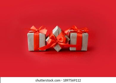 Close up composition with gifts on red background. Minimalist concept for Valentines day,  Mothers day, Women day or wedding. Greeting card with copyspace.