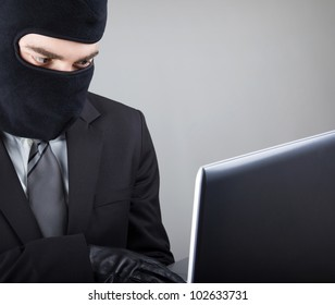 Close up of a computer hacker stealing data from laptop computer, isolated on white