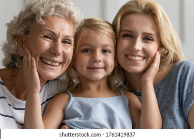 Close up concept image beautiful faces or 3 generations multi-generational relatives women portrait. Little granddaughter pose between old grandmother and young mother family smiling looking at camera